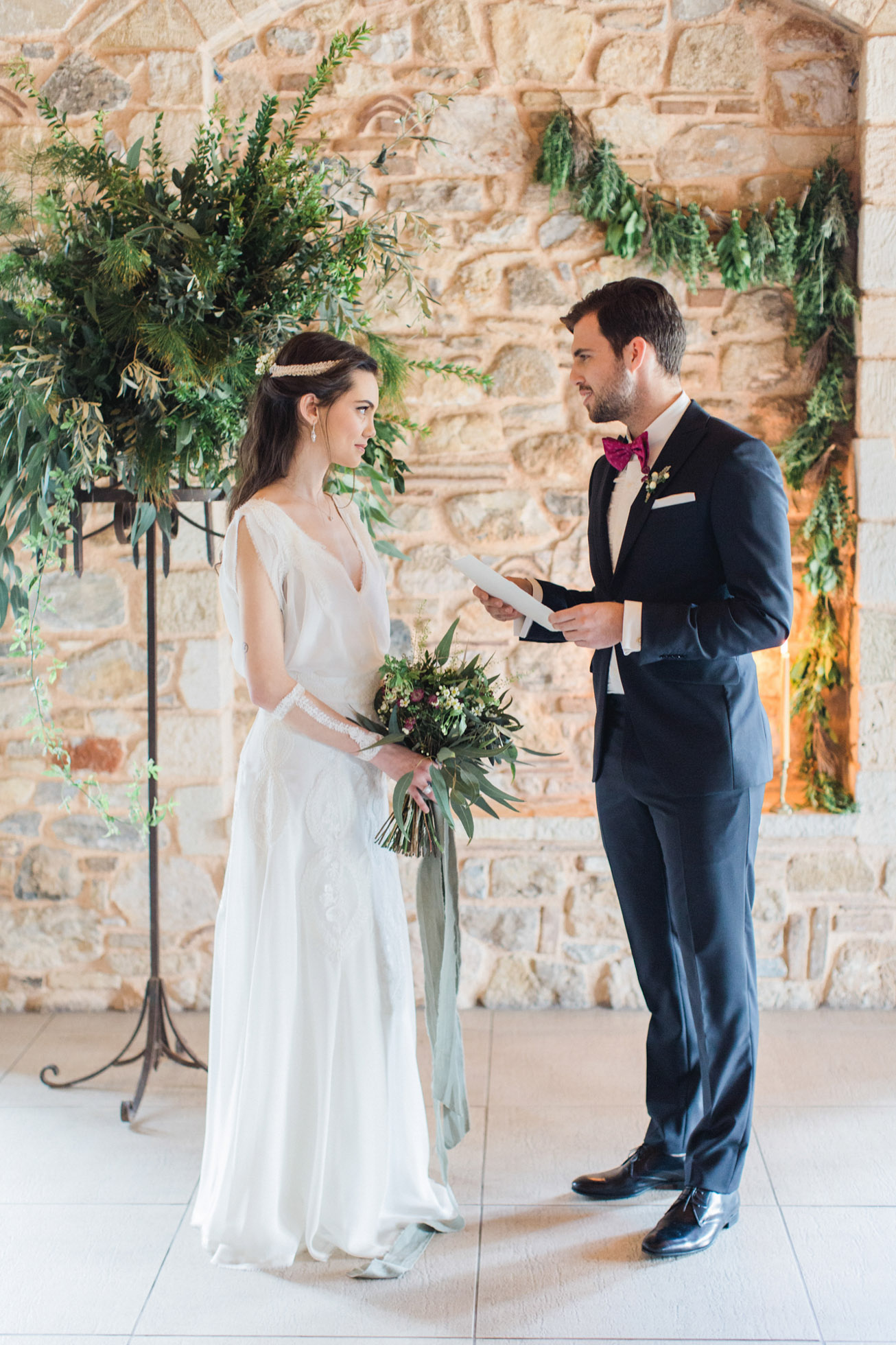 Bride And Groom During Their Wedding Ceremony Reading Vows Surrounded By The Decorations Of