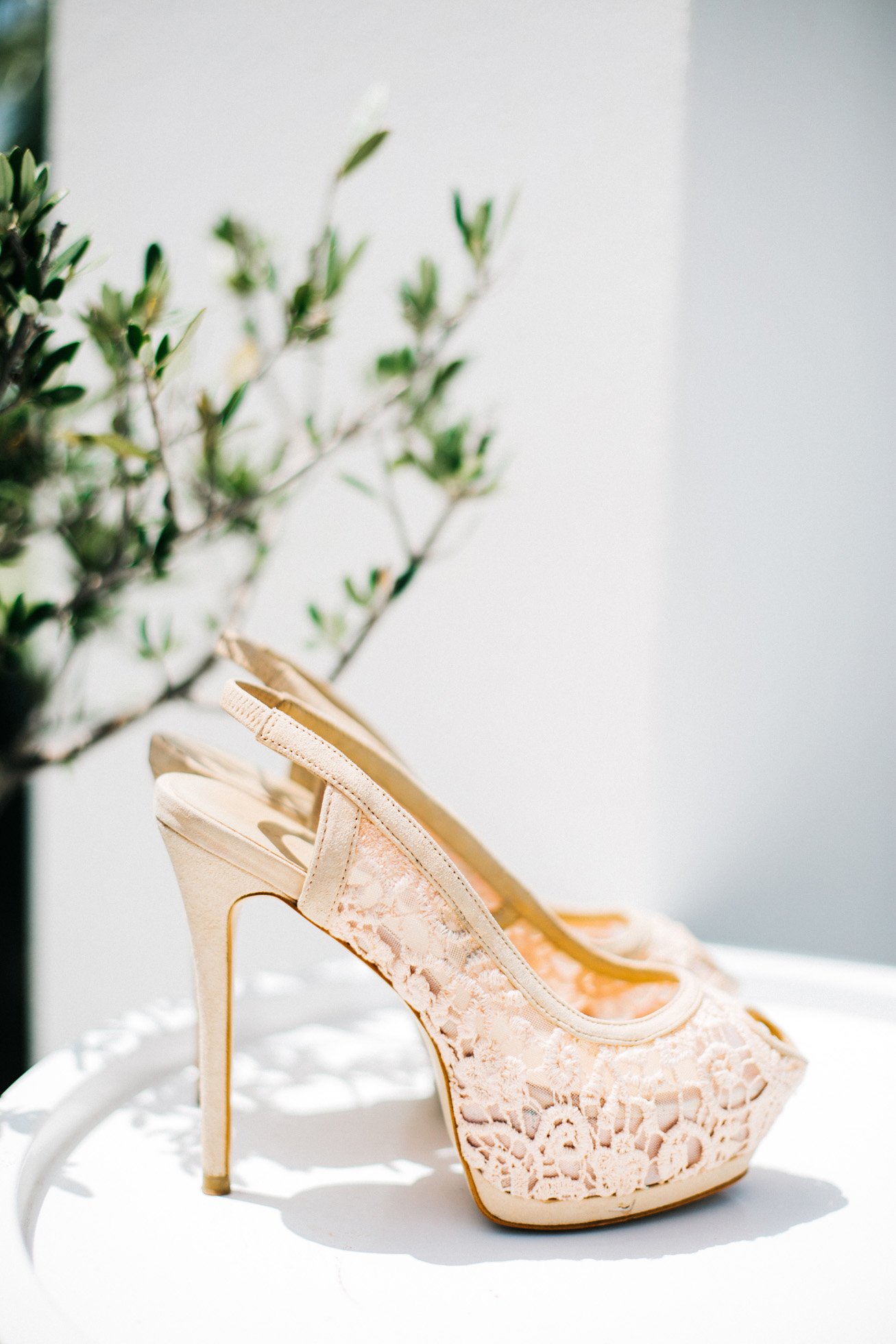 Wedding day image of a high heeled bridal shoes standing on white table near an olive tree.