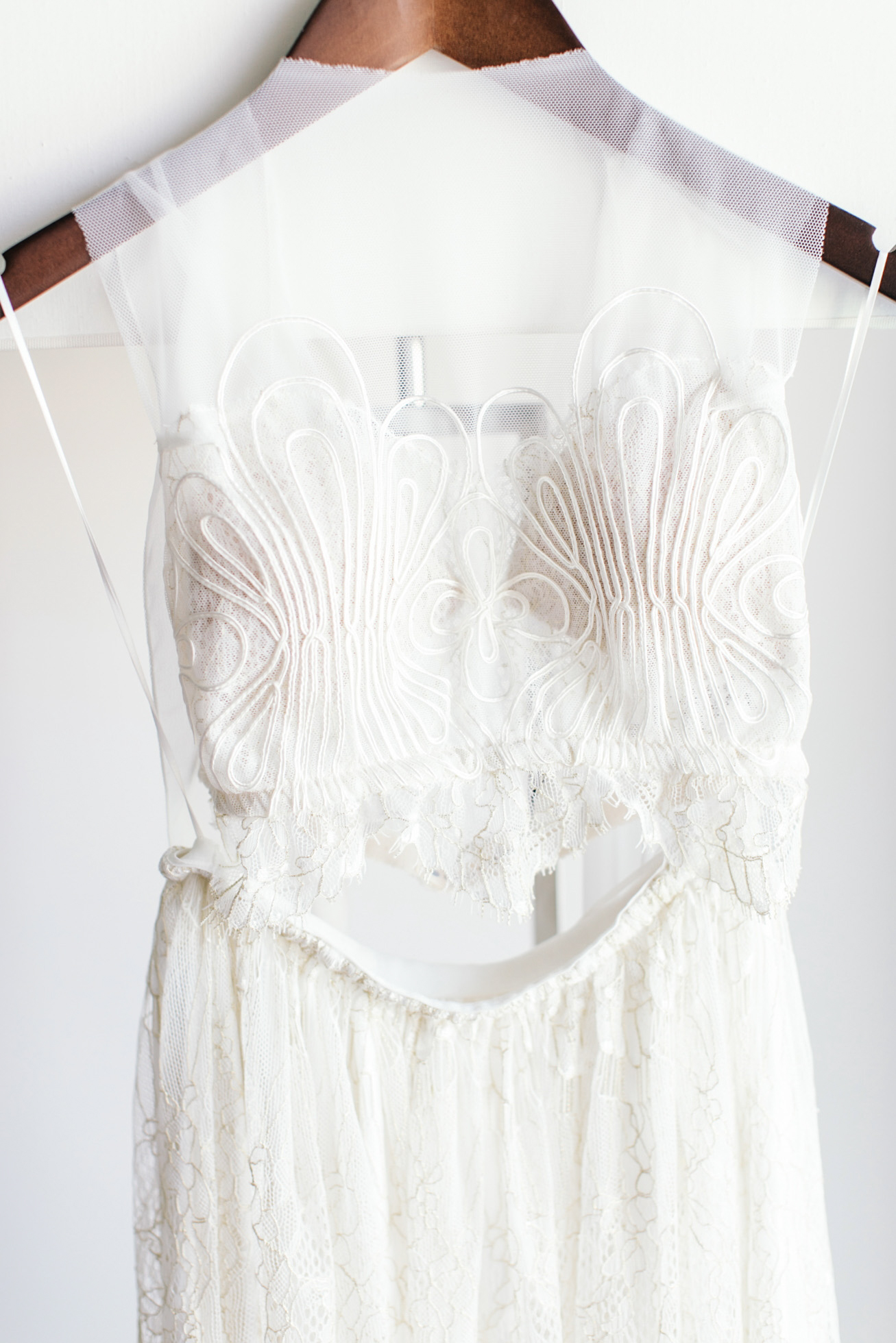 Intricate detail of a two piece boho bridal wedding gown photographer over delicate white background.