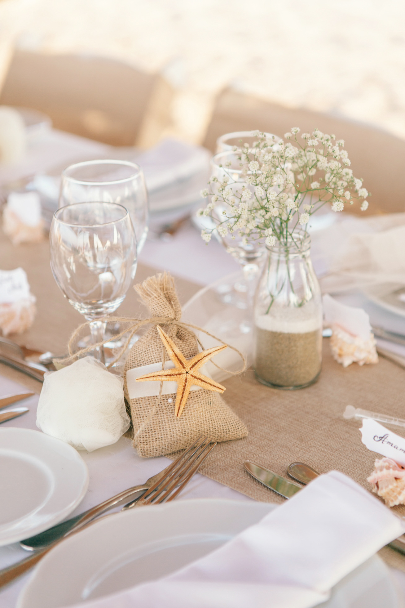 Beoho beach wedding reception details and tablescapes decorated and ready for the dinner reception, set up under a beduin tent and in the soft sand of the hotel beach.