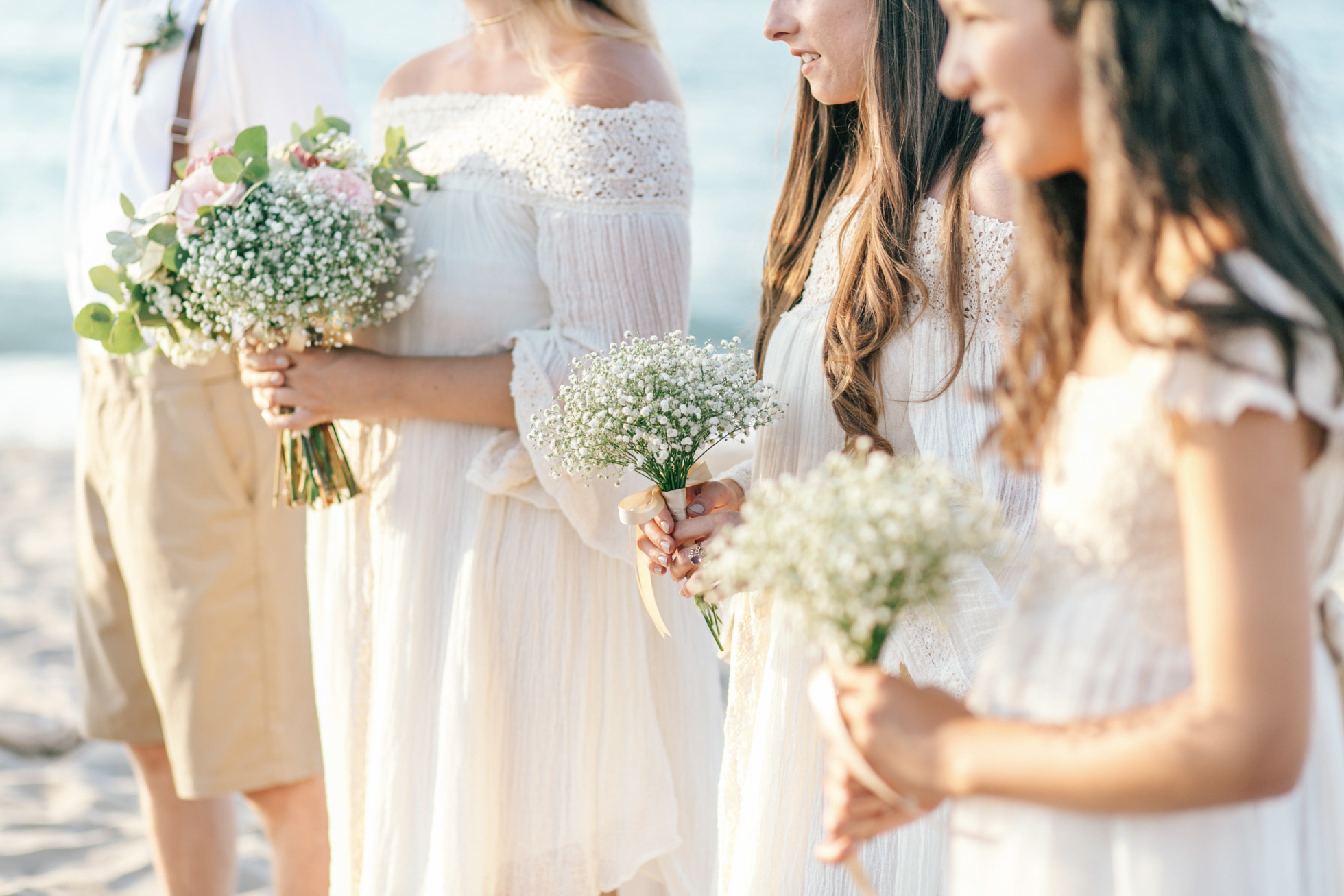 Close up photo of bridesmaids standing on the beach and holding their delicate understated bouquets of seasonal flowers.
