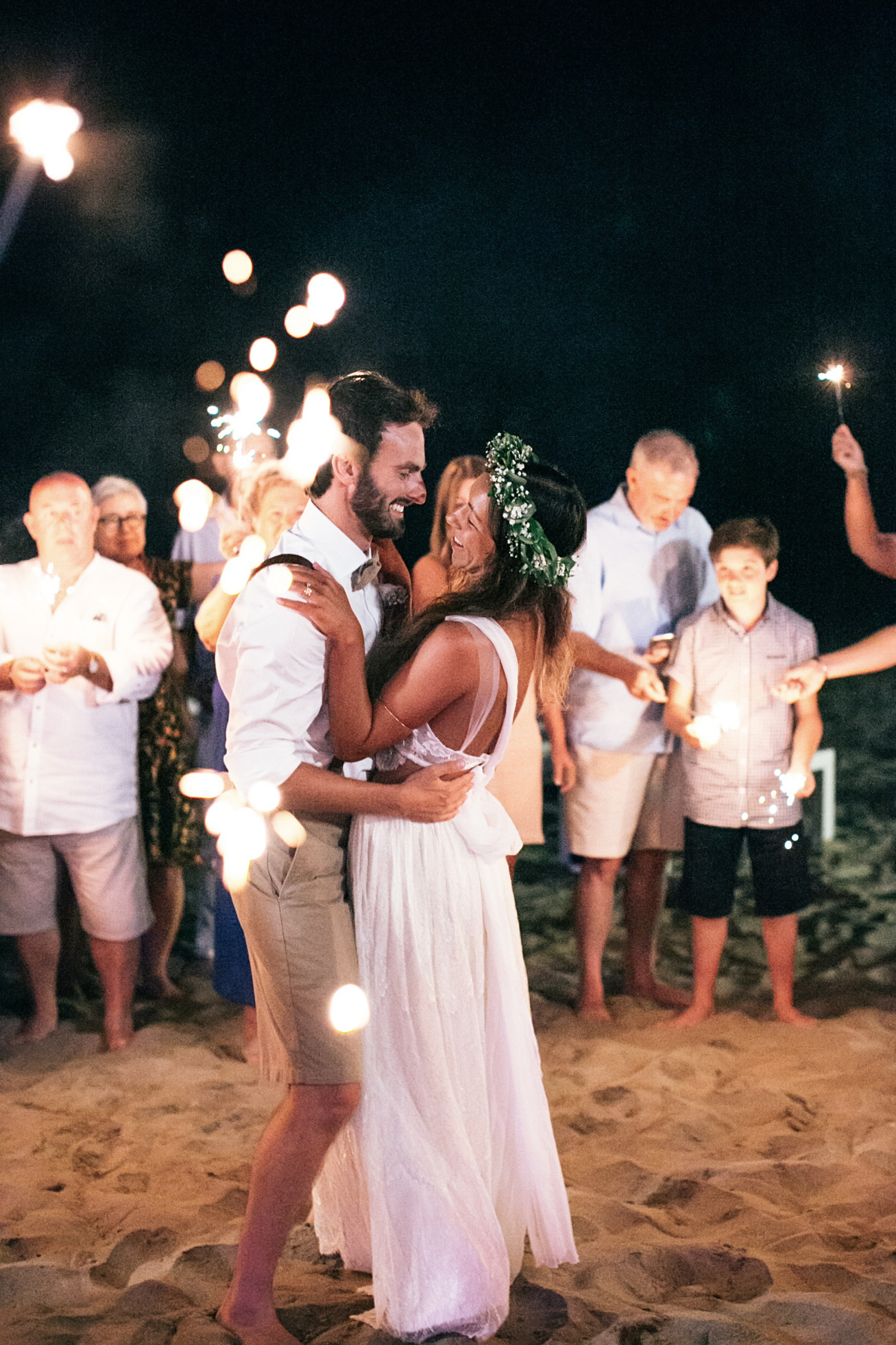 Professional photo of bride and groom during their first dance in the sand surrounded by happy wedding guests holding sparklers. The couple is dancing and laughing.
