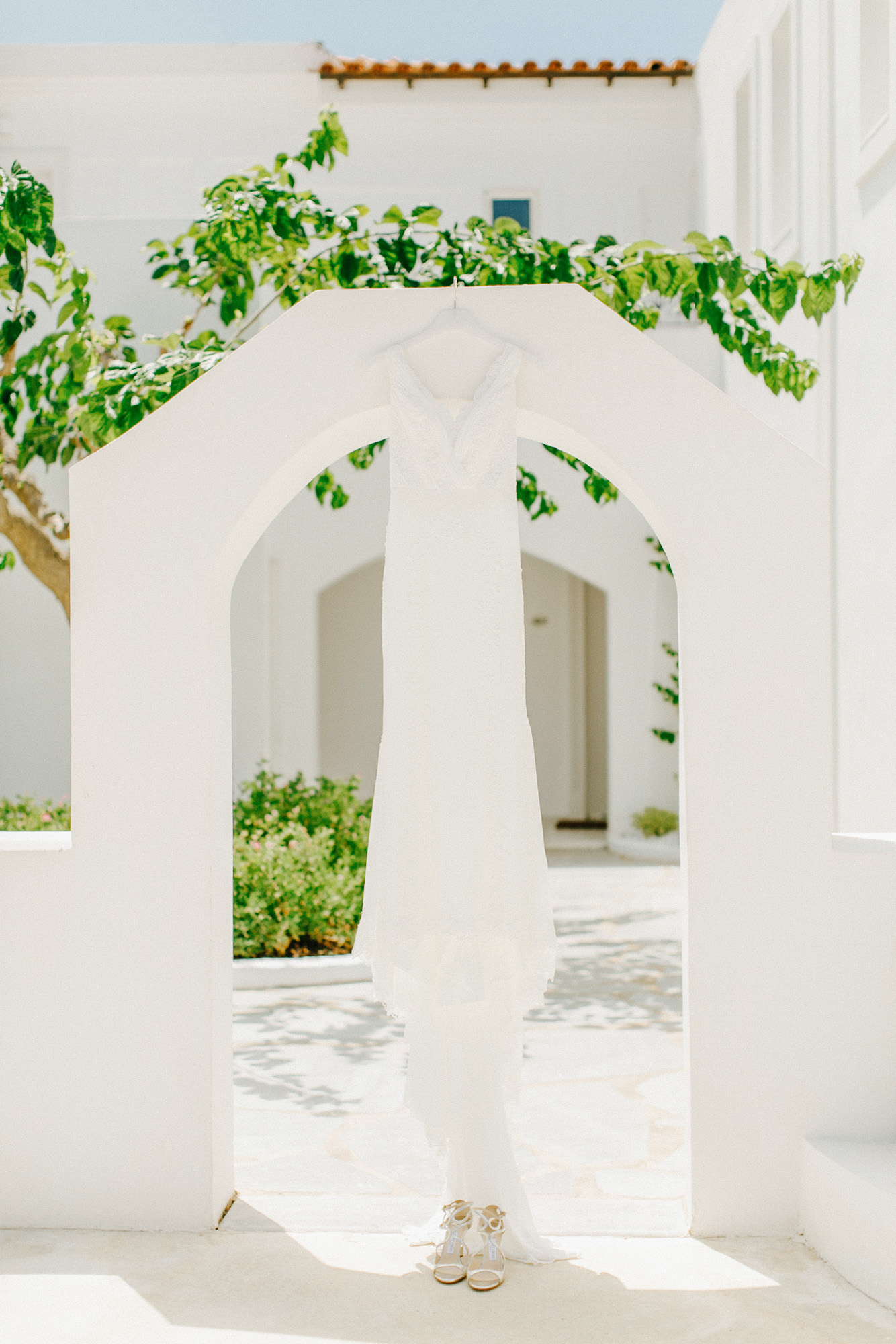 Pronovias bridal wedding dress hanging from a whitewashed doorway in Caramel luxury hotel in Crete.