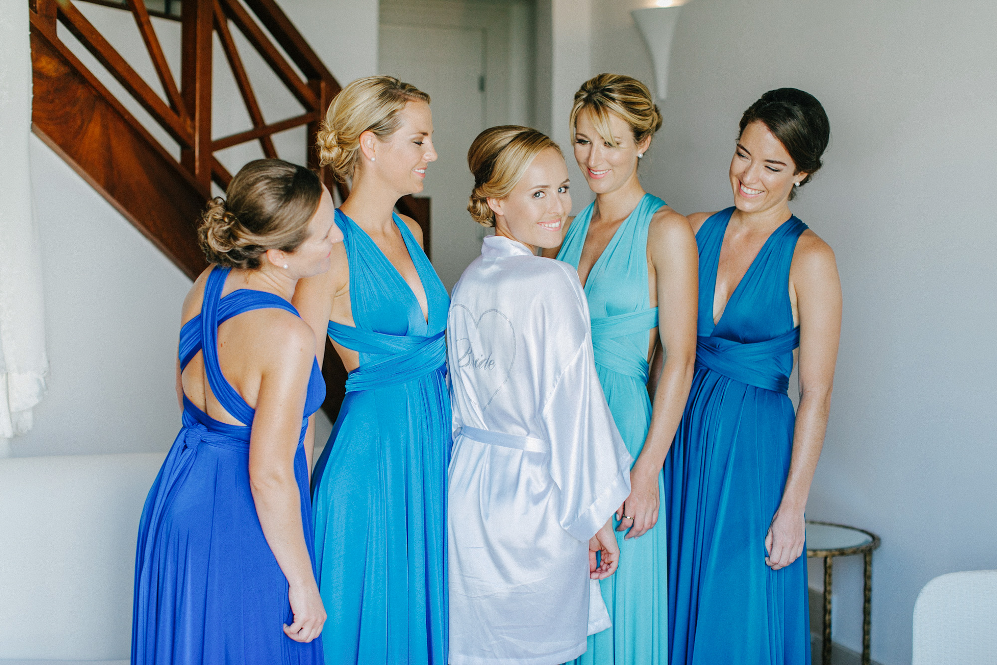 Professional portrait of four bridesmaids looking at the bride during bridal preparations in Caramel luxury hotel, they're wearing mismatched blue dresses, bride is looking at the wedding photographer smiling.