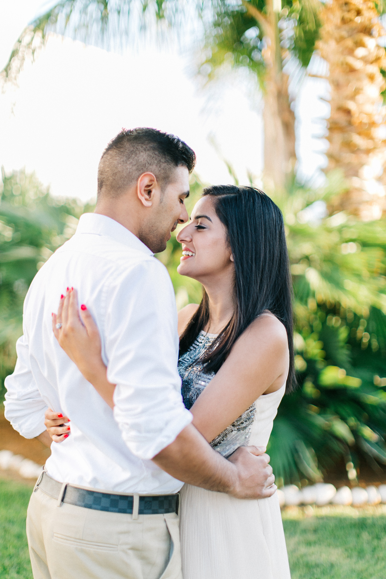 Professional photography portrait of engaged couple posing against the green lawn of their luxury resort in Crete during their pre wedding engagement photosession.