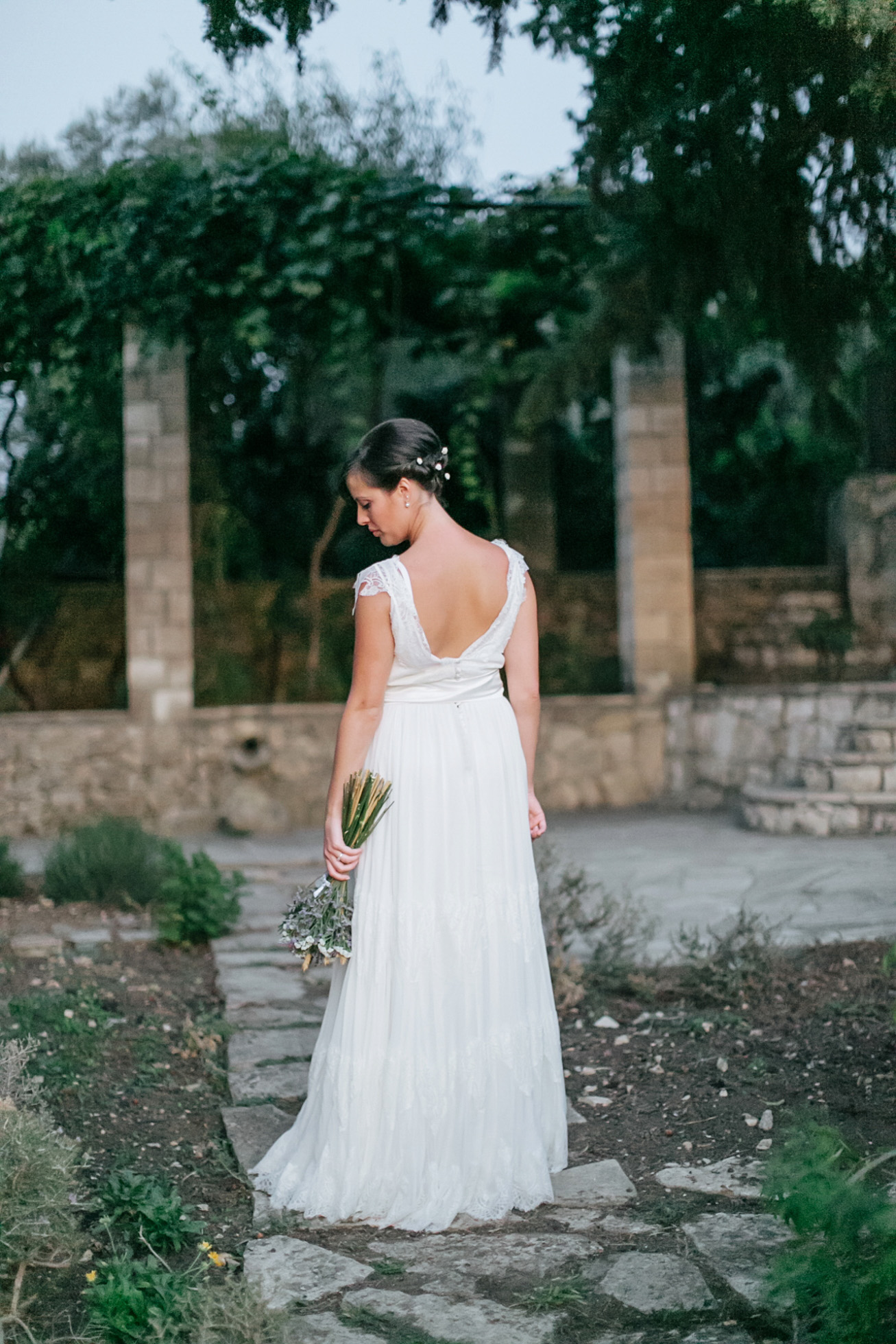 Fine art portrait of a beautiful trendy bride on her wedding day, posing for photos in Dourakis winery in Chania Crete captured by wedding photographer team.