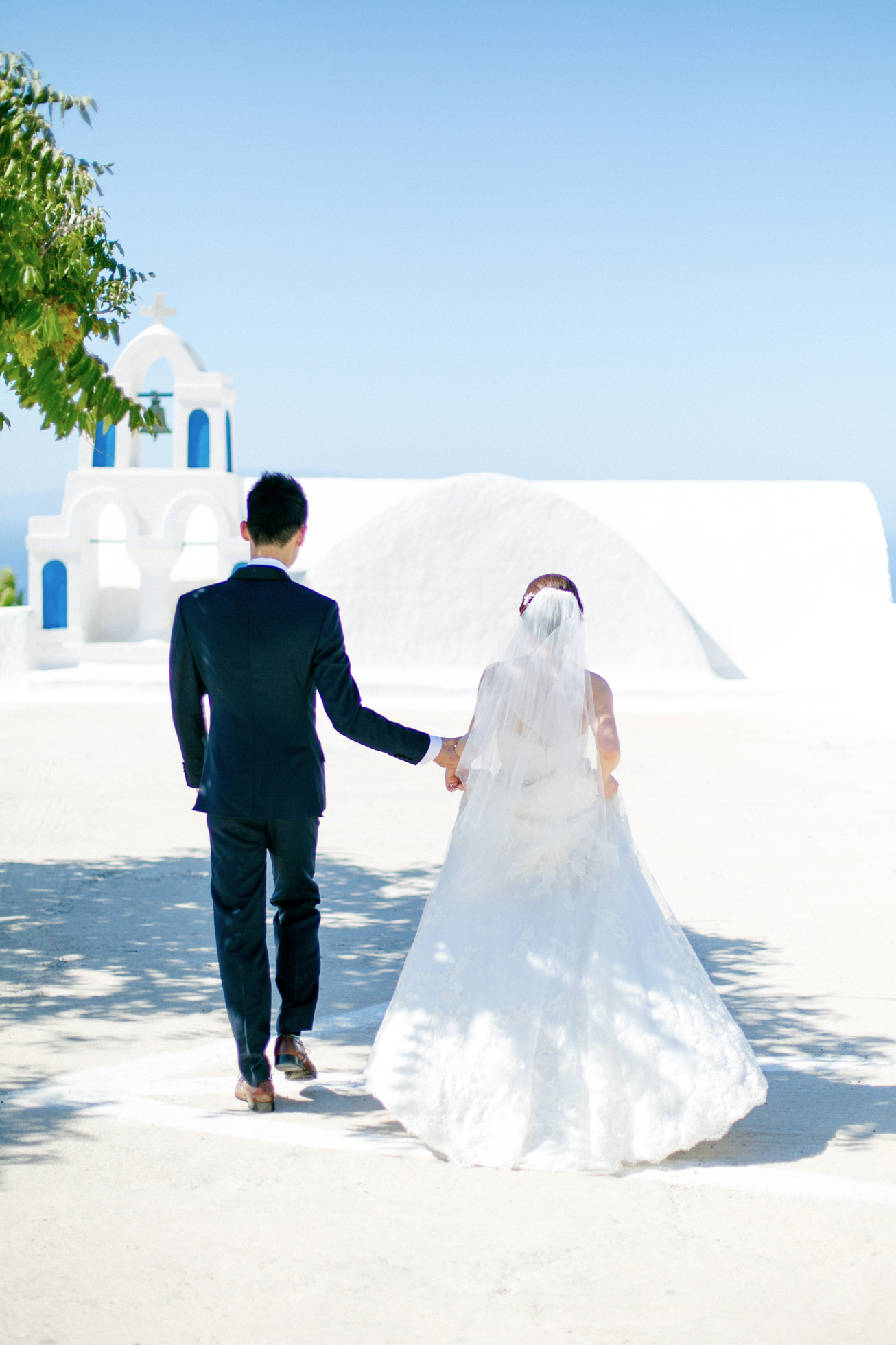 Professional Santorini wedding day photoshoot, groom and bride are walking with the picturesque background of Oia, Santorini church and clear blue skies.