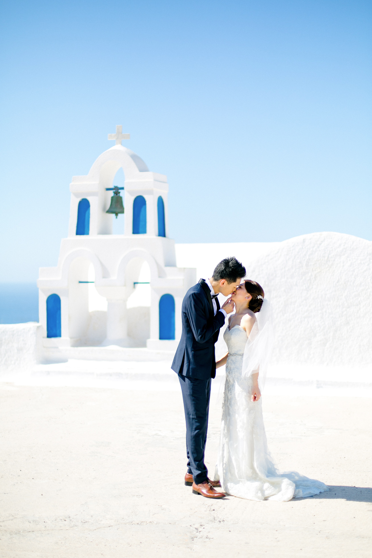 Professional Santorini wedding day photoshoot, groom and bride are kissing with the picturesque background of Oia, Santorini church and clear blue skies.