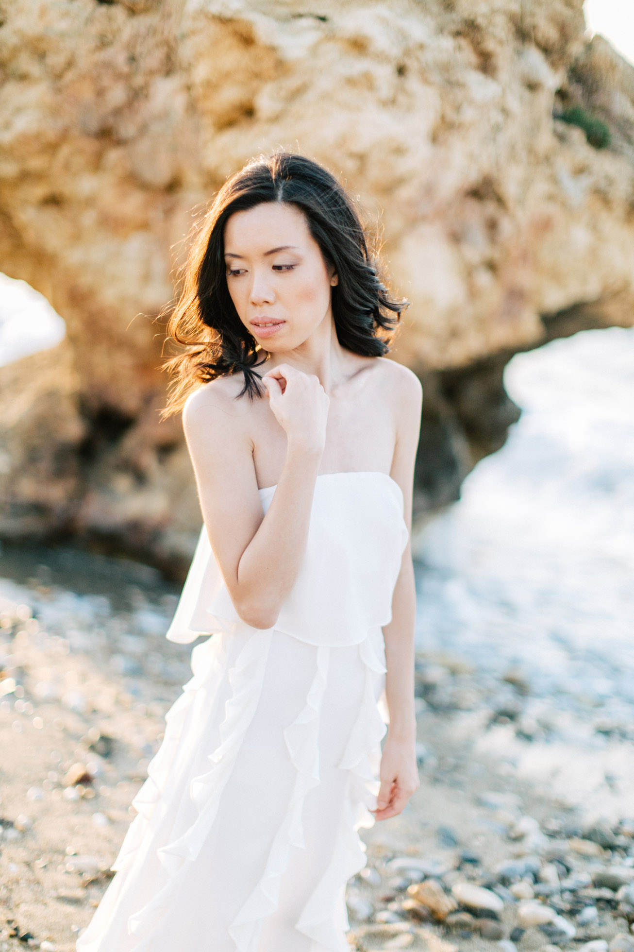 Beautiful destination bride wearing bridal dress is posing for professional photographer team during beach wedding photoshoot on the secluded shores of Rethymno town, Crete, Greece.