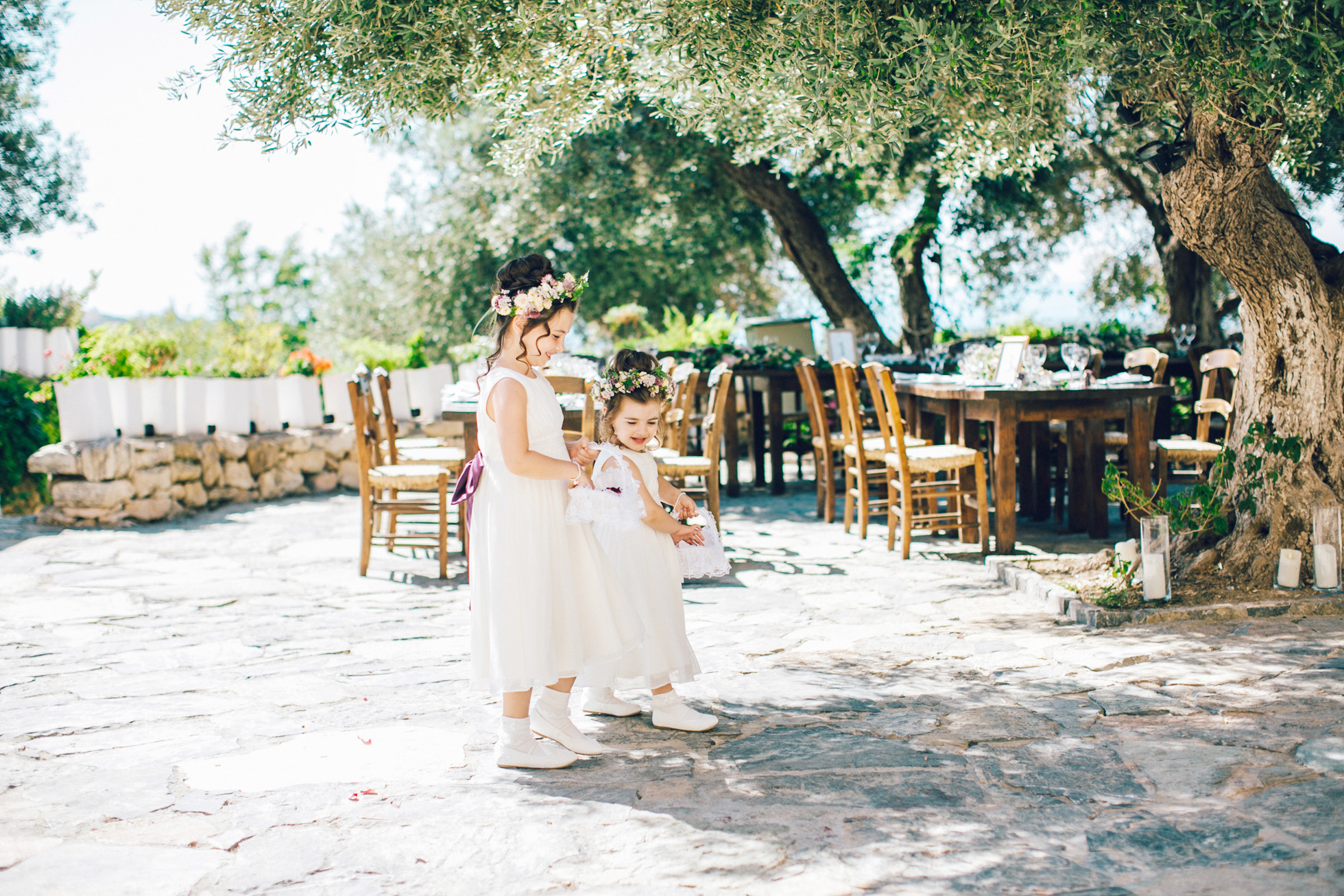 Candid image of two cute flower girls walking down the aisle into the wedding ceremony on a destination wedding day in Agreco Farm in Crete.