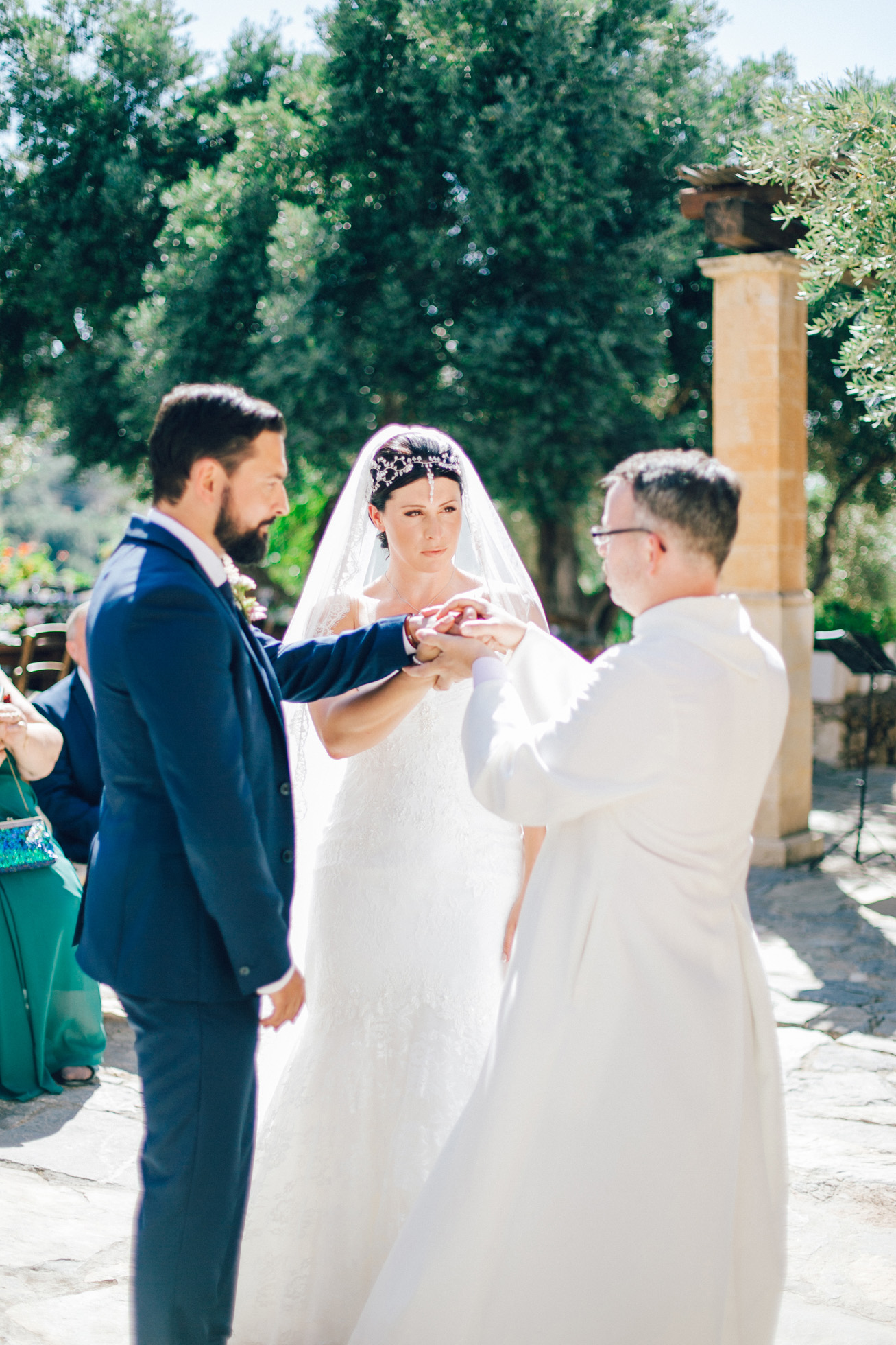 Candid image of an elegant bride and groom getting married in Agreco Farm in Crete, Greece, captured by their wedding photographer.
