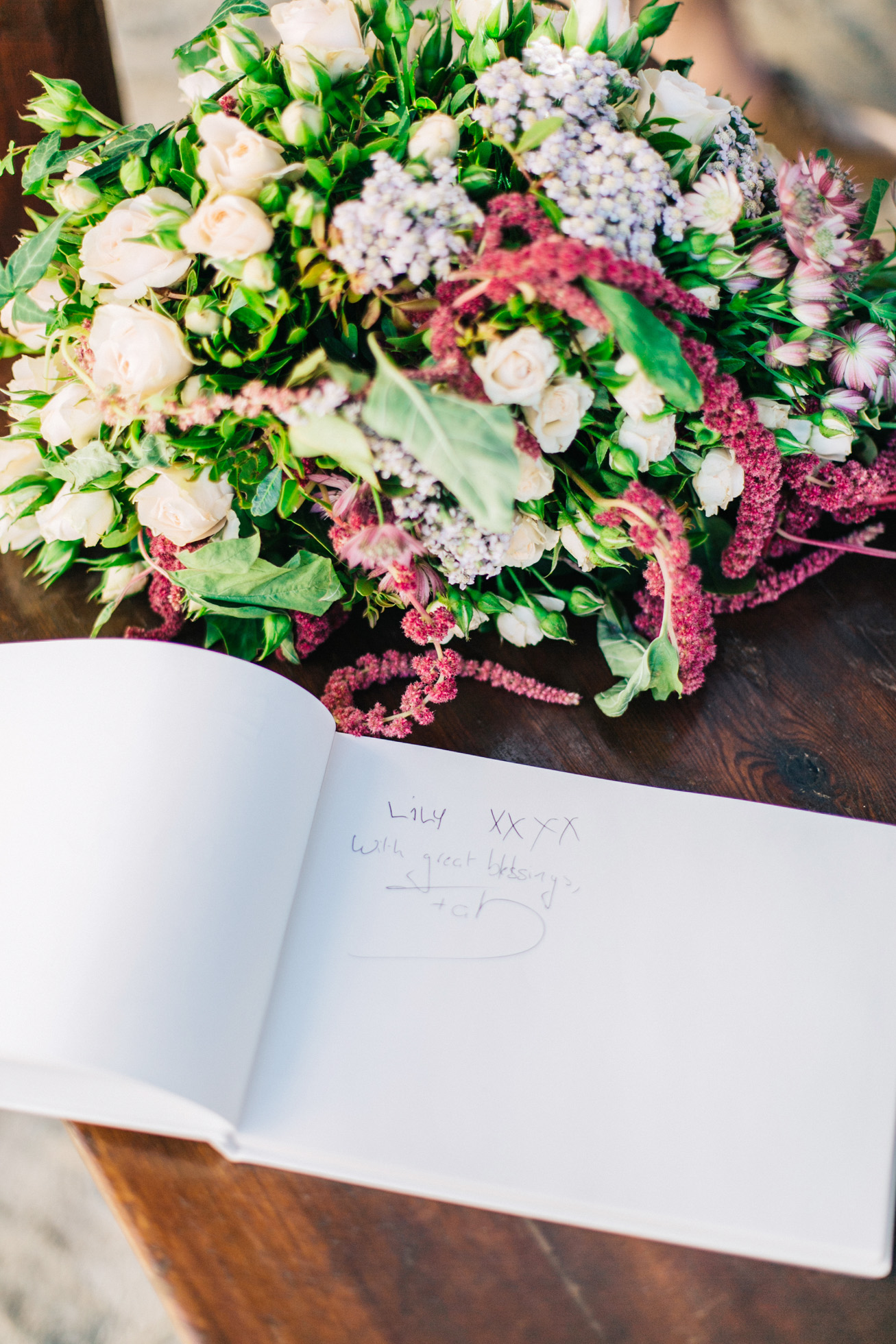 Rich floral decorations and wish book details created by Fabio Zardi and captured by wedding photographer during a destination wedding in Agreco farm in Crete.