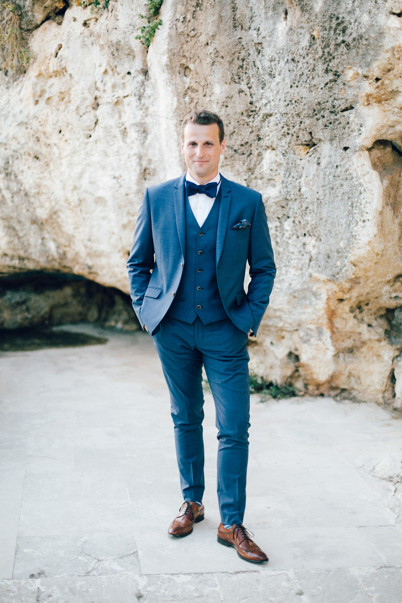 Portrait of an elegant modern groom on his wedding day in Crete posing for professional photographer.