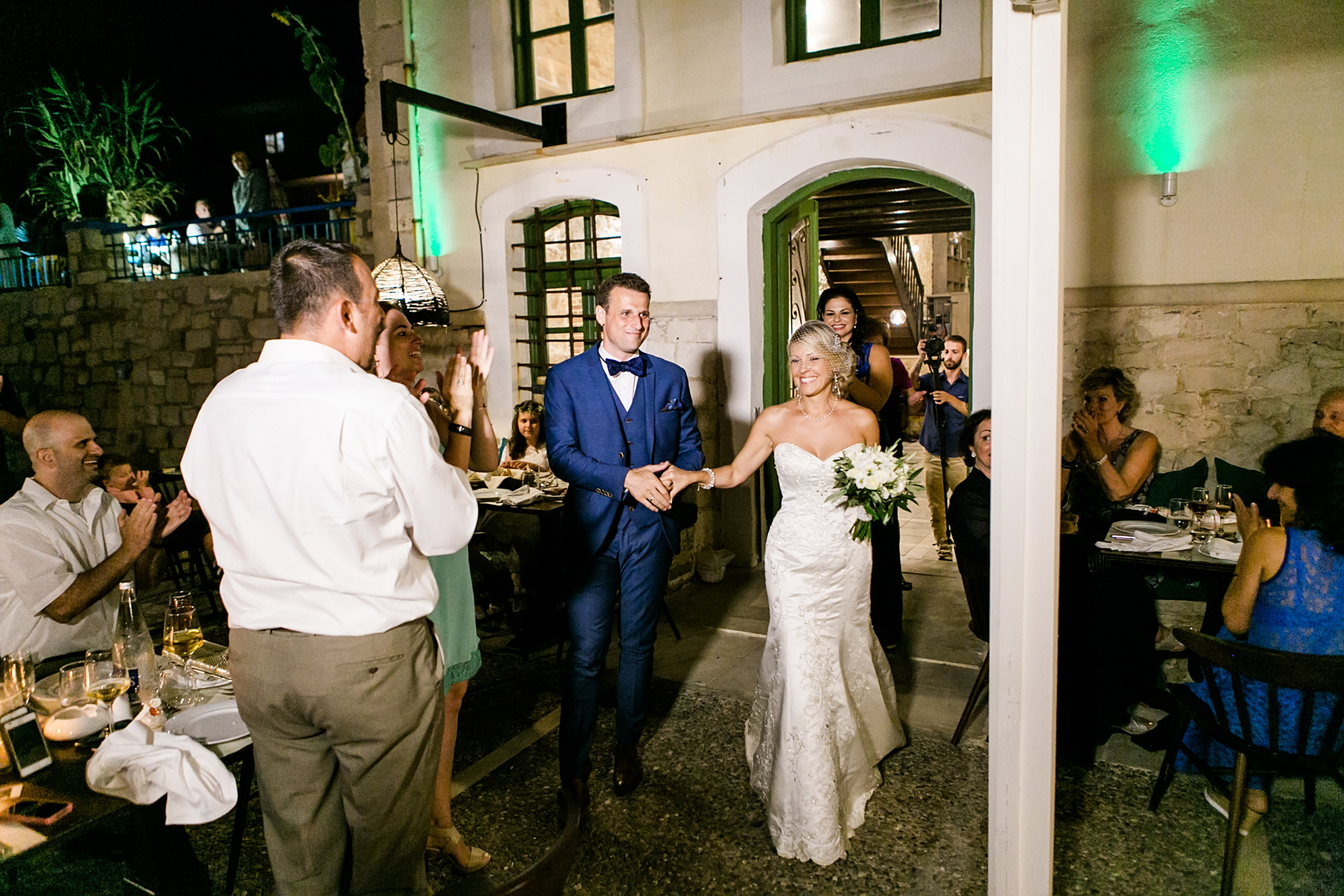 Destination wedding reception image of a restaurant wedding dinner including bride and groom's great entrance, cake cut, speeches and first dance. Captured by professional wedding photographer in Crete Greece.